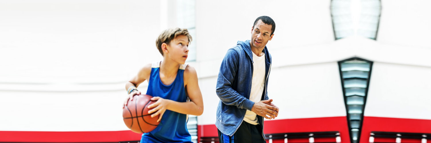 coach and his tstudent playing basketball